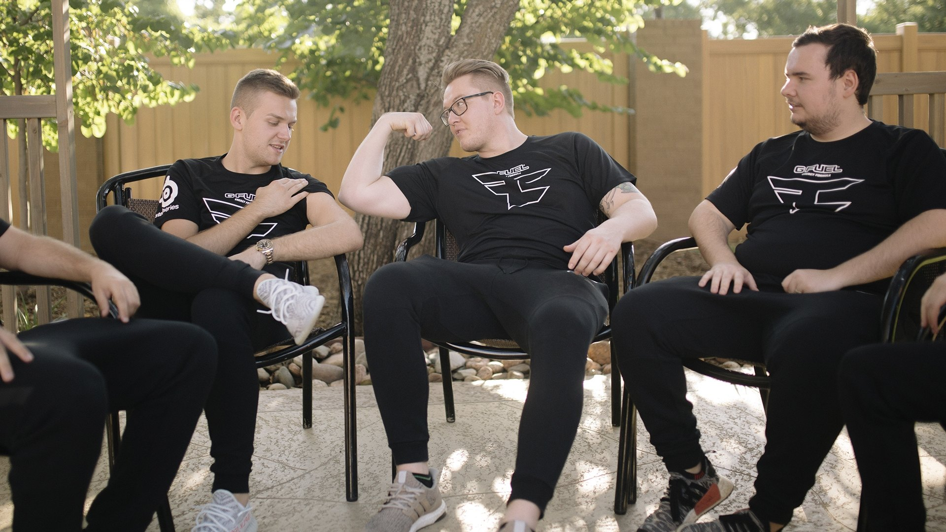 FaZe team members sitting in a circle relaxed in a yard