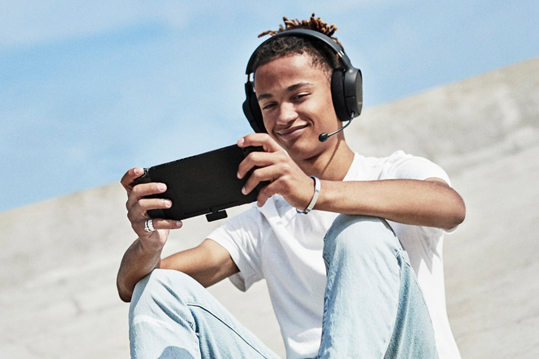 Gamer outdoors playing the Nintendo Switch game console while wirelessly listening via the Arctis 1 Wireless for PS4 gaming headset and dongle