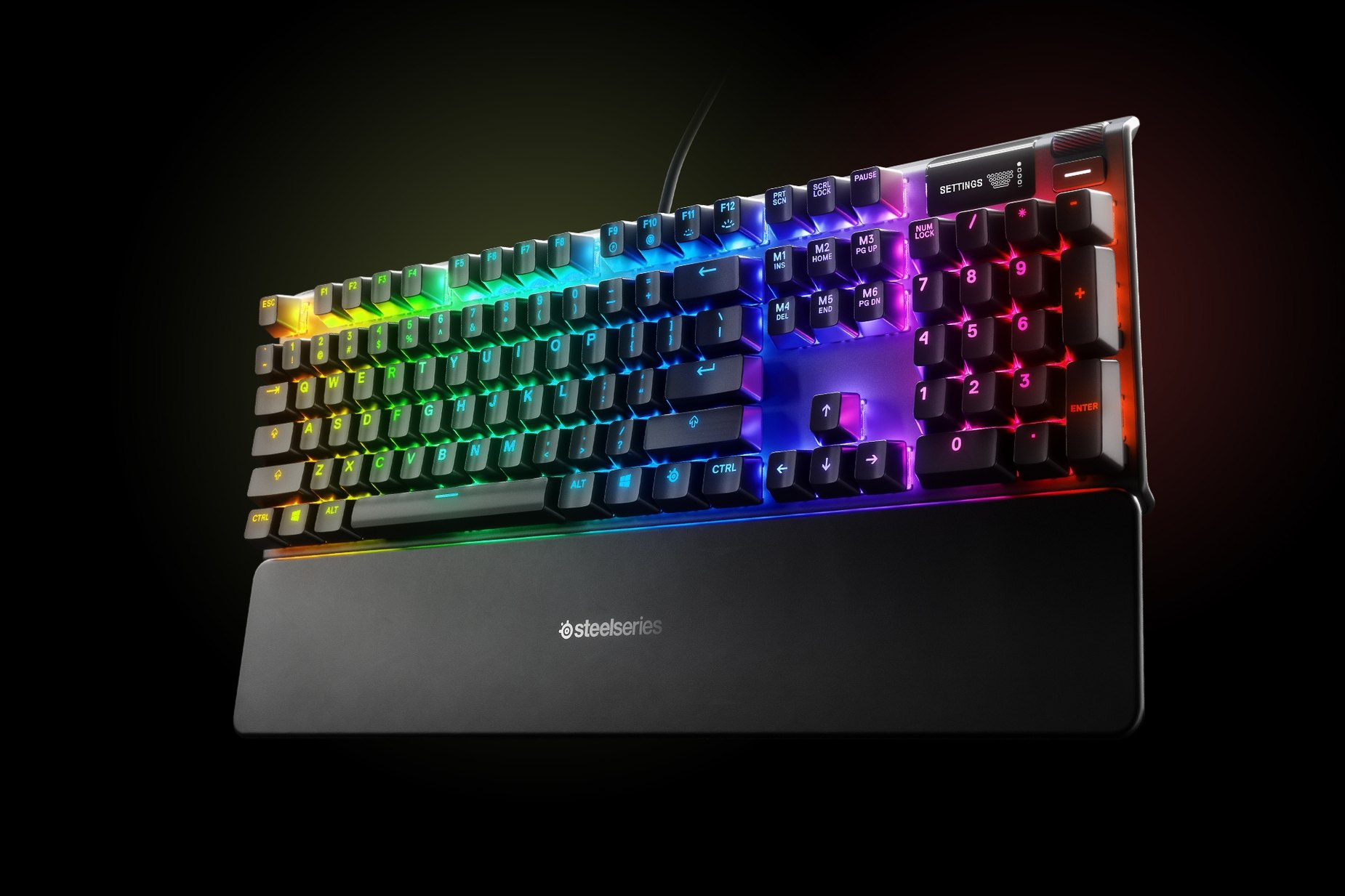 US English - Apex 7 (Blue Switch) gaming keyboard with the illumination lit up on dark background, also shows the OLED screen and controls used to change settings and adjust audio