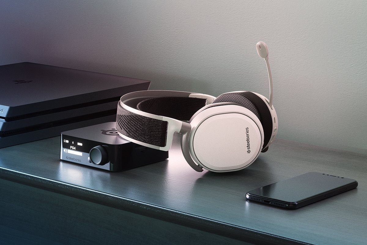 Arctis Pro Wireless White leaning on it's transmitter on a console with an iPhone and PlayStation visible