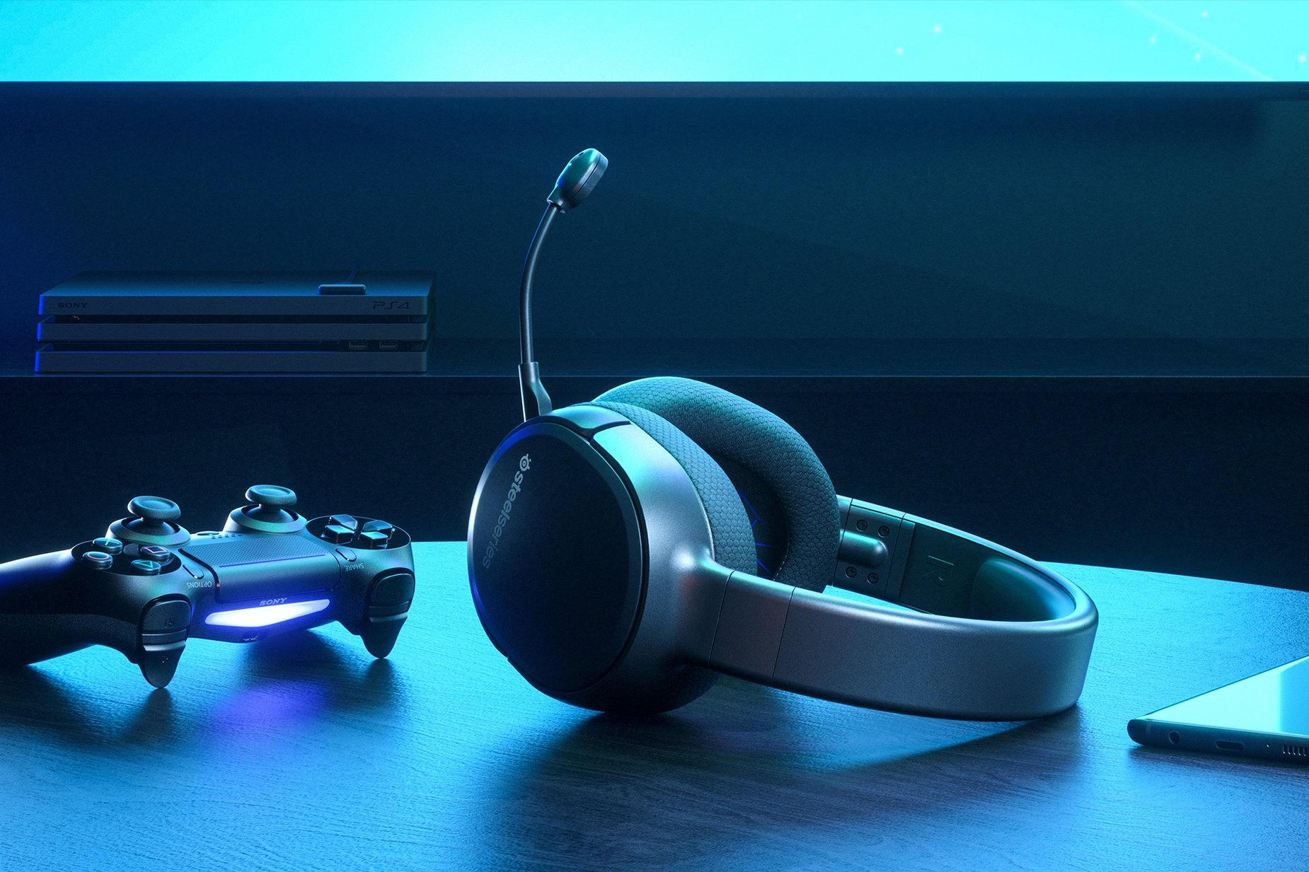 Arctis 1 Wireless for PS4 gaming headset on table with a Playstation controller and a PS4 in the background
