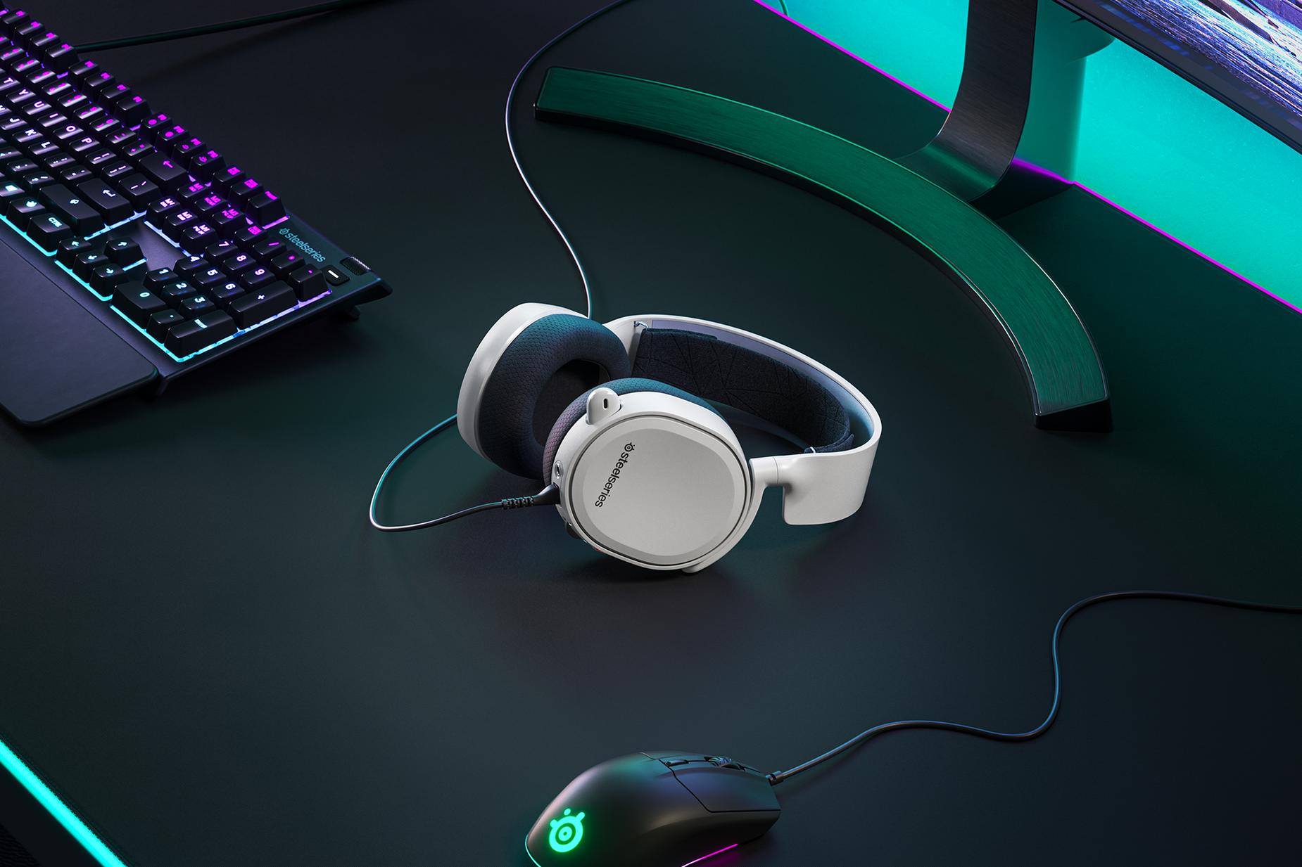 白いArctis 3コンソールヘッドセットが机の上に置いてあり、輝くSteelSeries製マウスとRGB照明SteelSeries製キーボードがヘッドセットの横に置いてあります。
