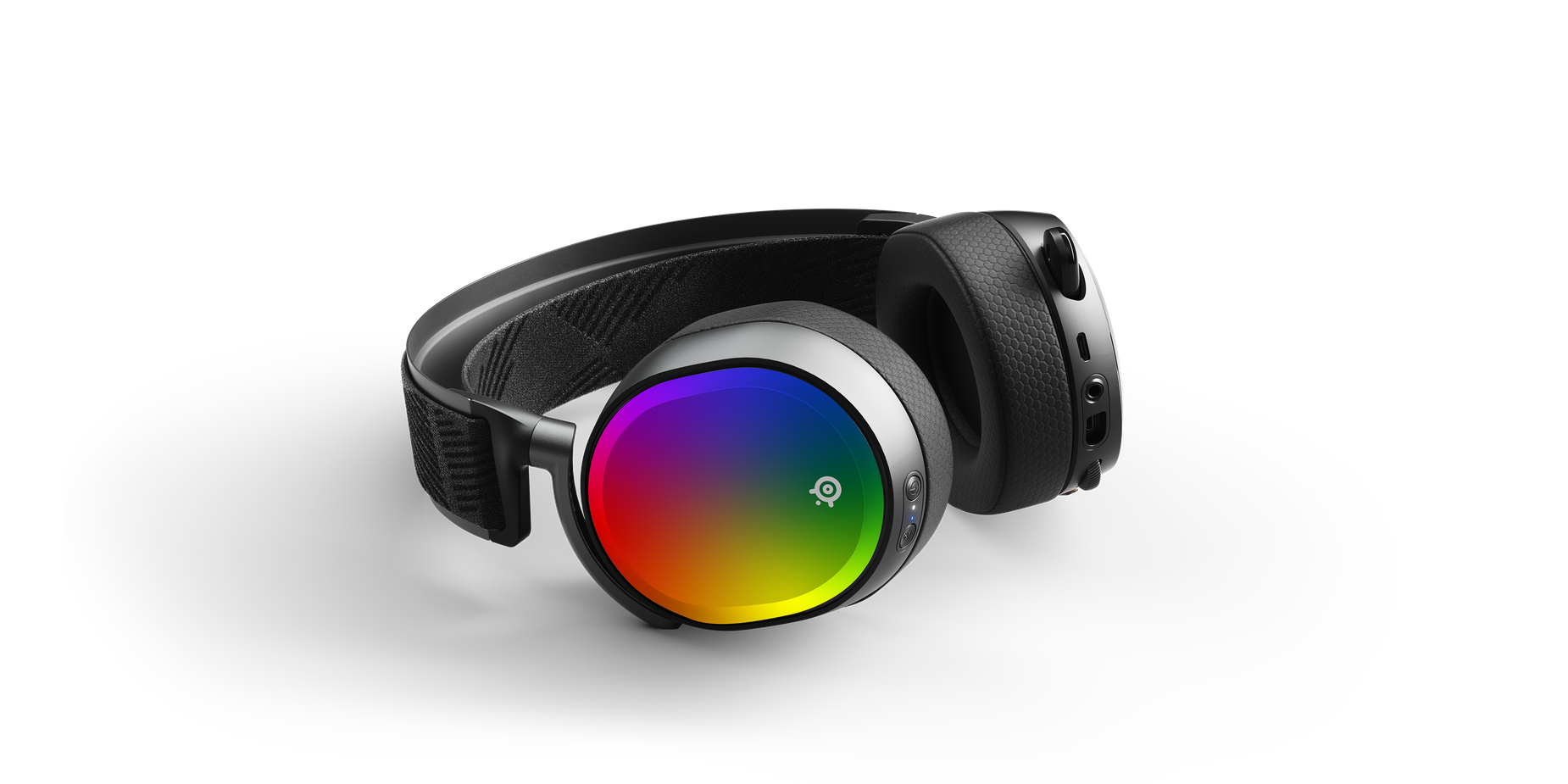 An Arctis headset laying down on a surface with the For Pride speaker plates.