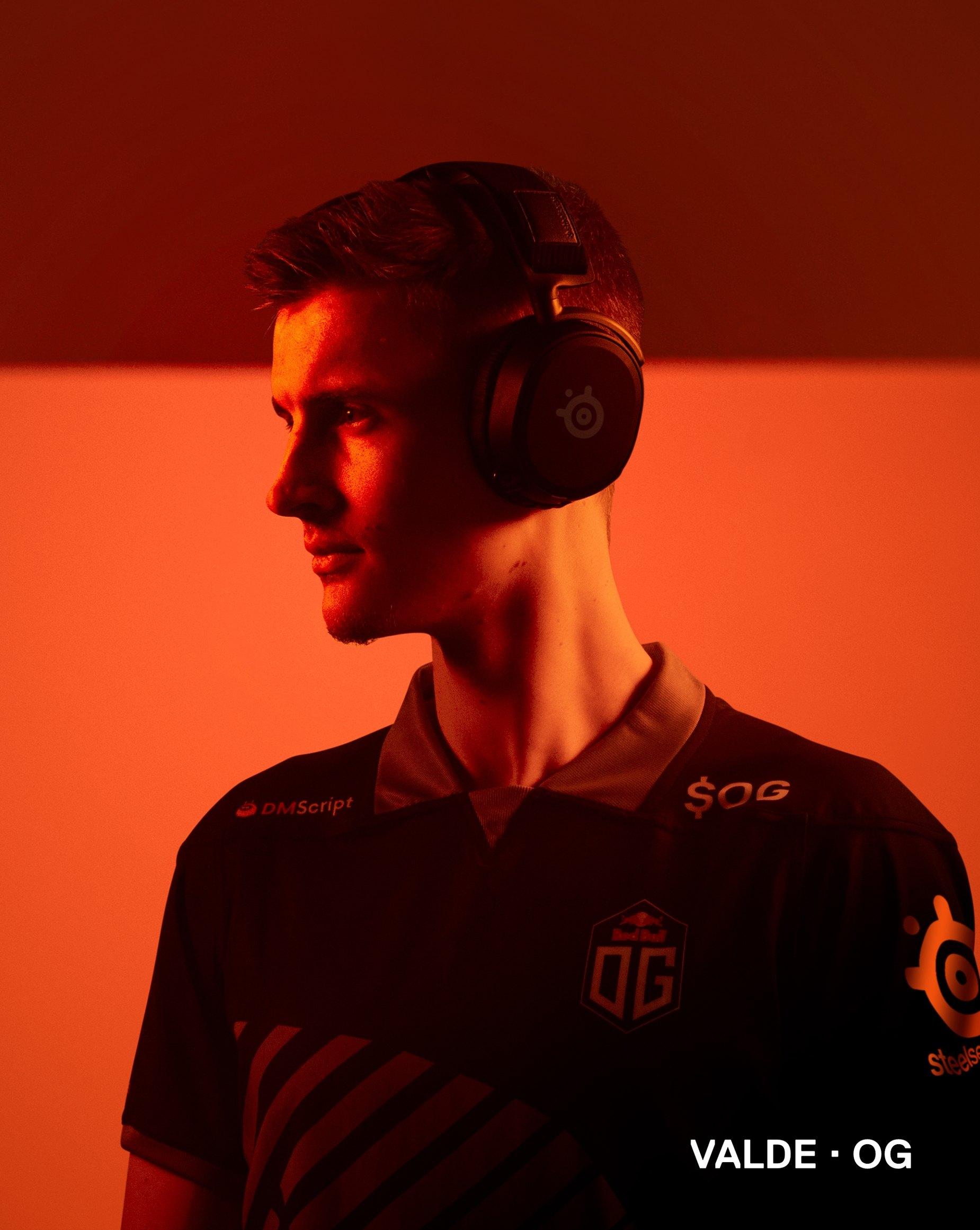 OG player Valde stands against an orange background wearing the Arctis Prime headset.