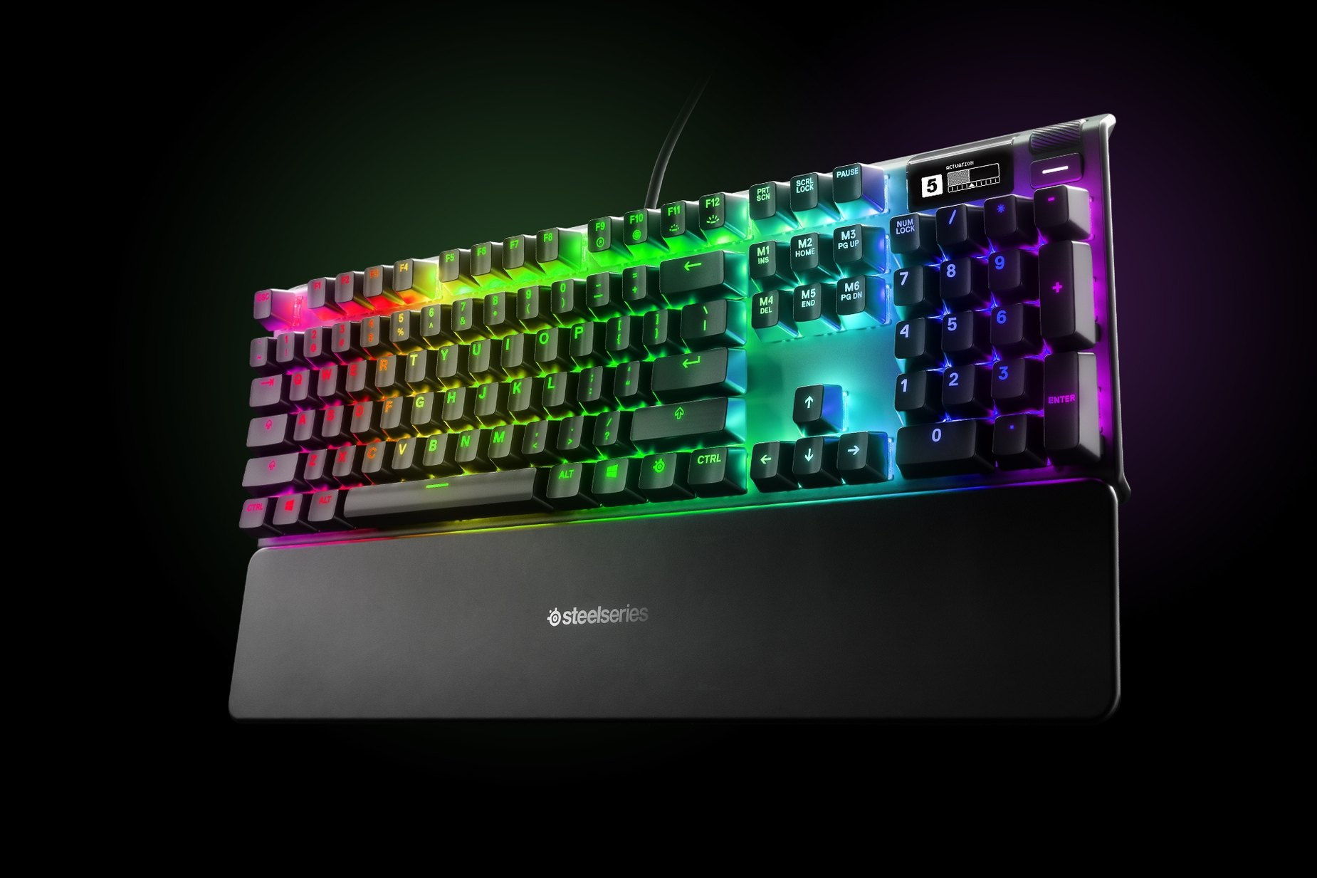 German - Apex Pro gaming keyboard with the illumination lit up on dark background, also shows the OLED screen and controls used to change settings, switch actuation, and adjust audio