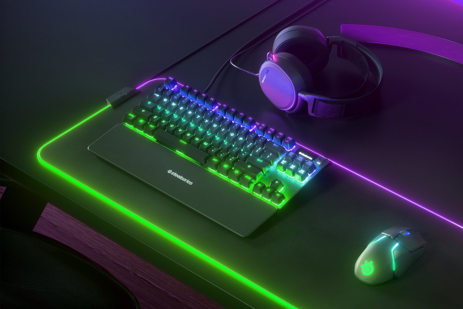 French - Apex Pro TKL gaming keyboard on a desk with a gaming mouse, both on top of a large mousepad and a SteelSeries gaming headset next to them