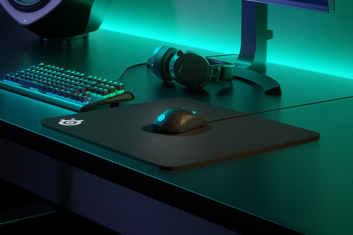 QcK Heavy on desk with mouse, keyboard, headset, and monitor