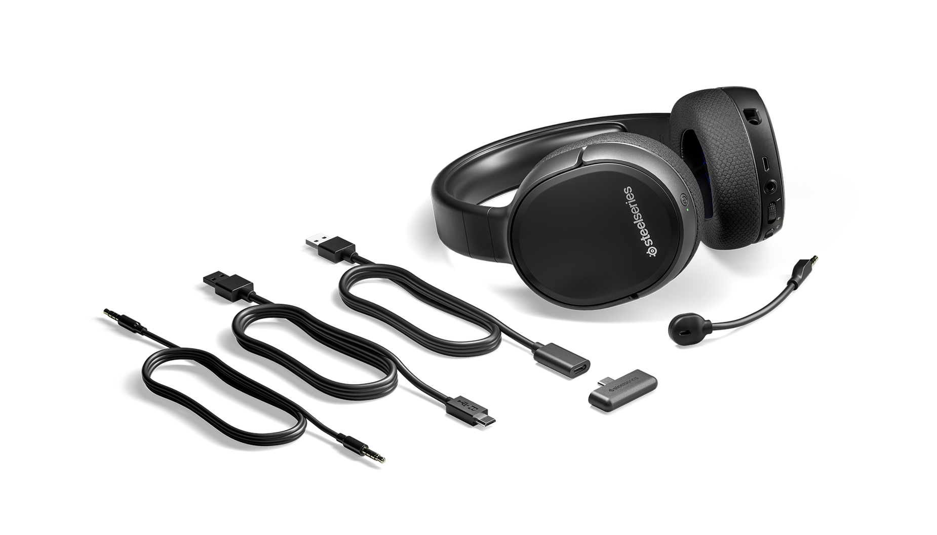 The Arctis 1 Wireless for PS4 gaming headset surrounded by all the box contents including extra cables and the wireless dongle