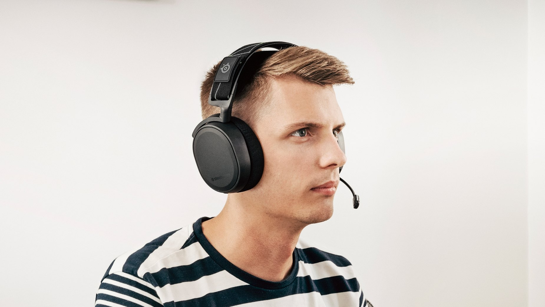 Gamer wearing Arctis 7 headset with microphone extended