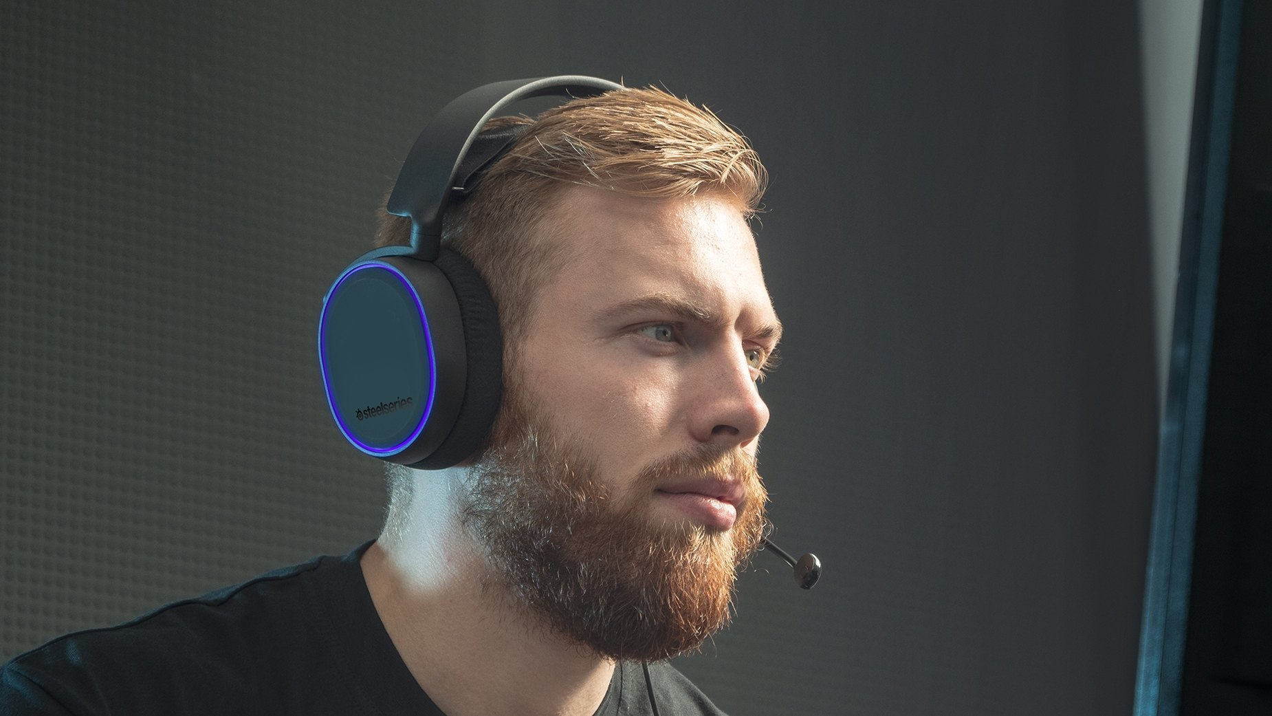 Gamer wearing Arctis 5 headset with RGB illumination around the ear cup