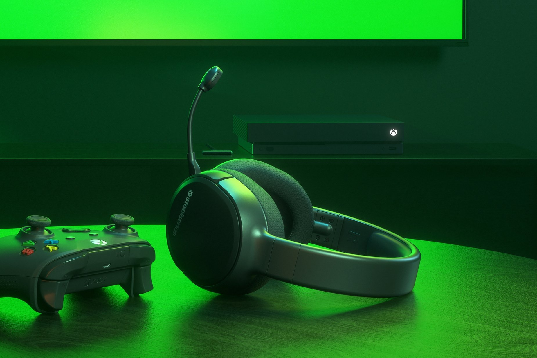Arctis 1 Wireless for Xbox gaming headset on table with a Xbox controller and an Xbox game console in the background
