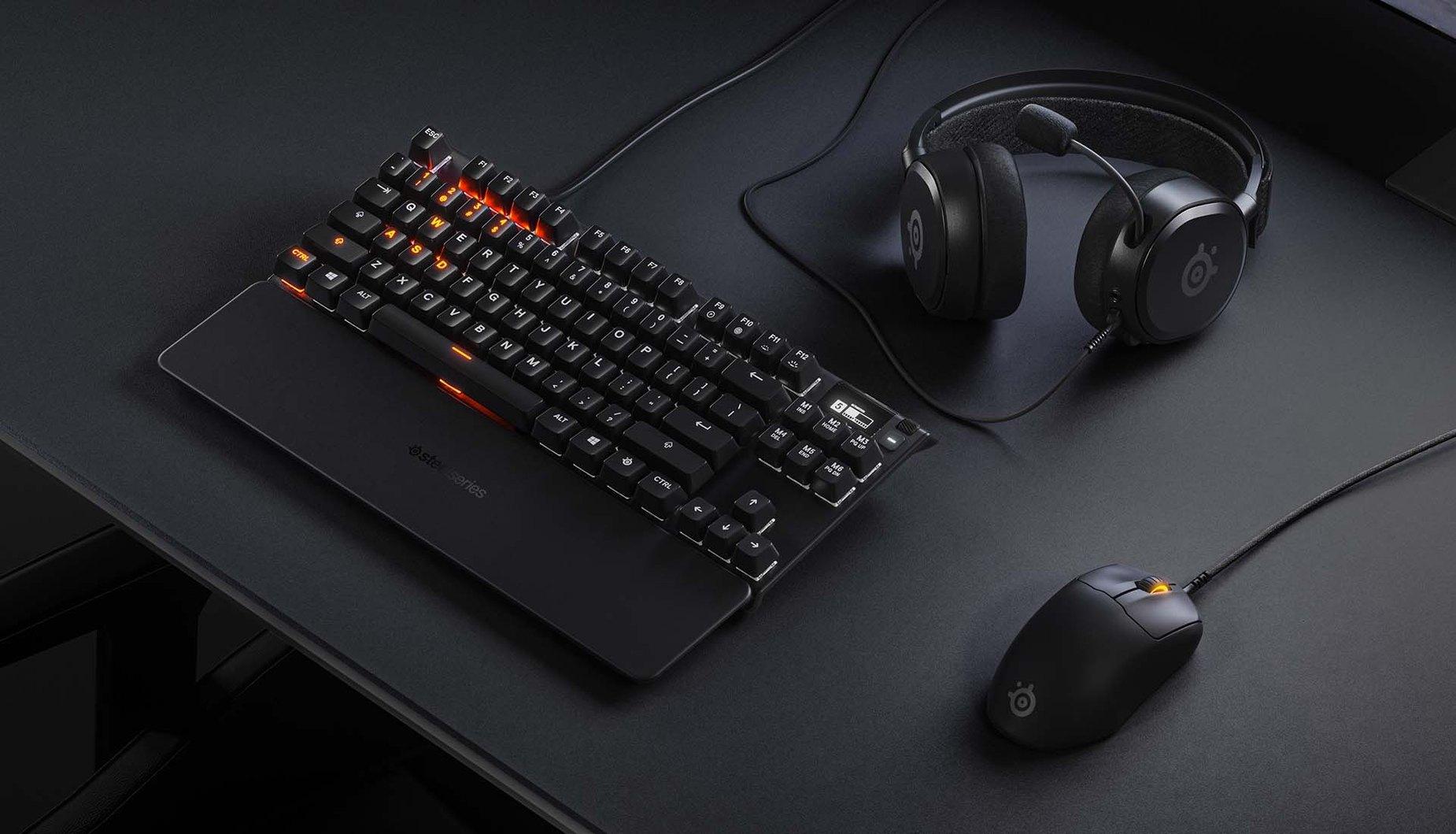 Overhead view of Prime Mini mouse sitting beside a sleek SteelSeries keyboard.