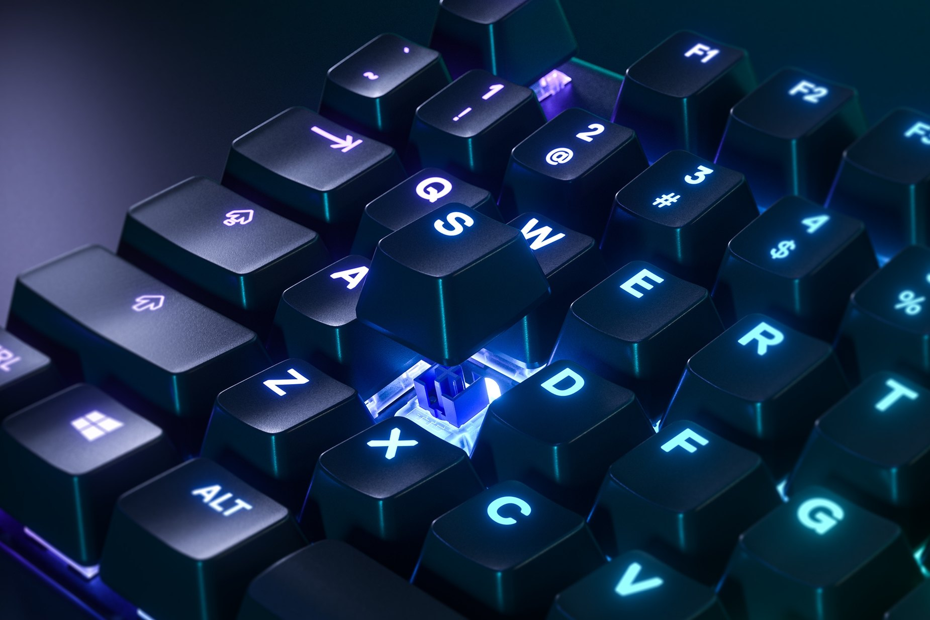 Zoomed in view of a single key on the Apex 5 gaming keyboard, the key is raised up to show the SteelSeries Hybrid Mechanical RGB Switch underneath