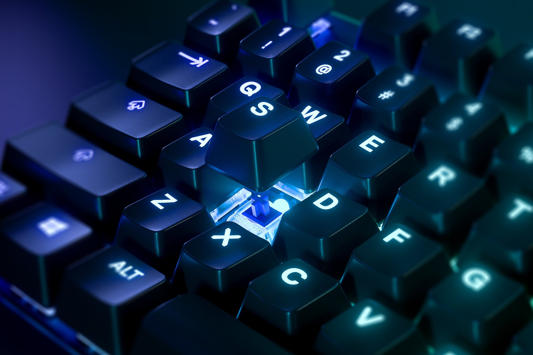 Zoomed in view of a single key on the Japanese-Apex 7 TKL (Blue Switch) gaming keyboard, the key is raised up to show the SteelSeries QX2 Mechanical RGB Switch underneath