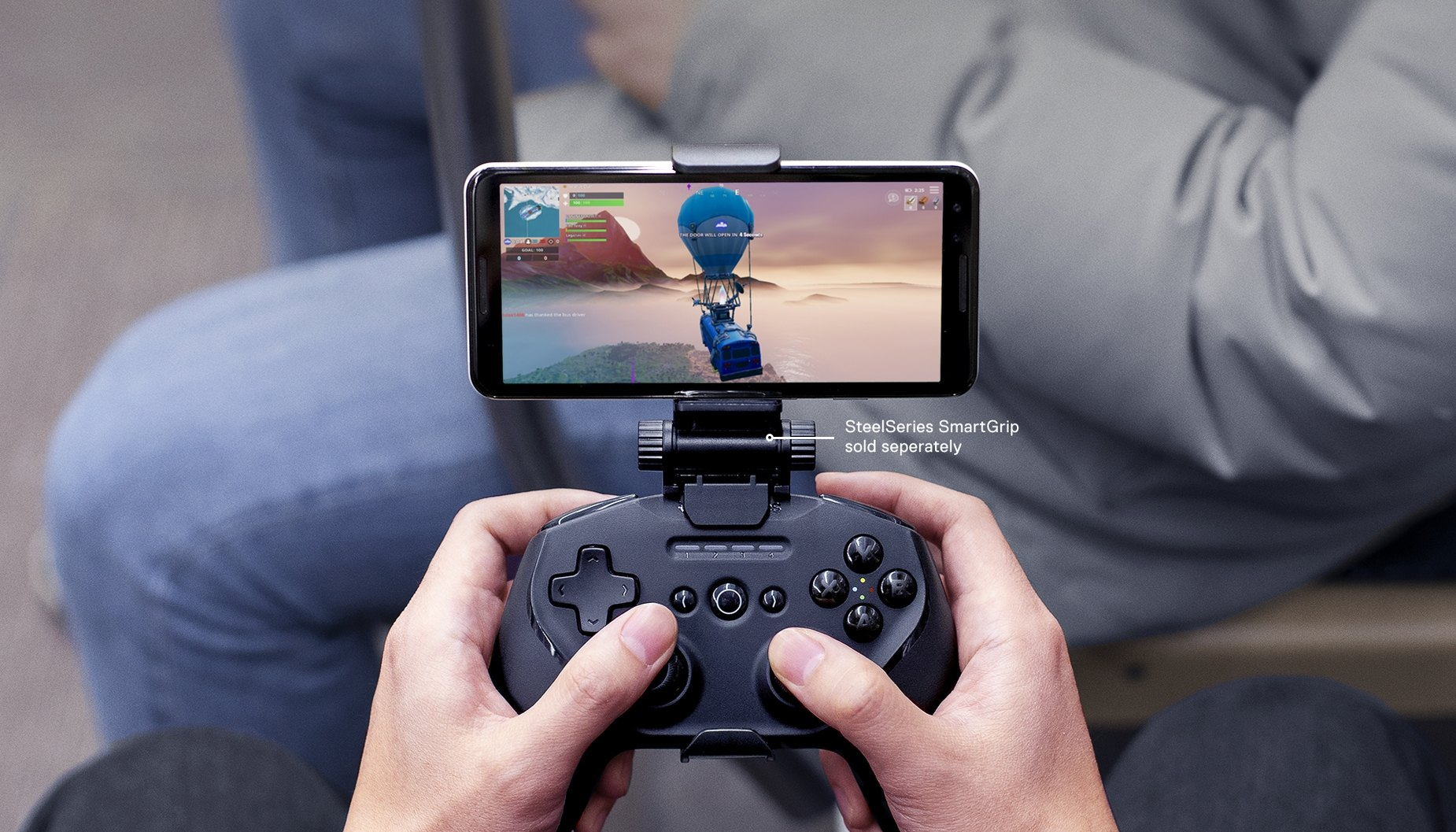 Hands holding Stratus Duo for Windows, Android™, and VR with SmartGrip attachment playing Fortnite mobile