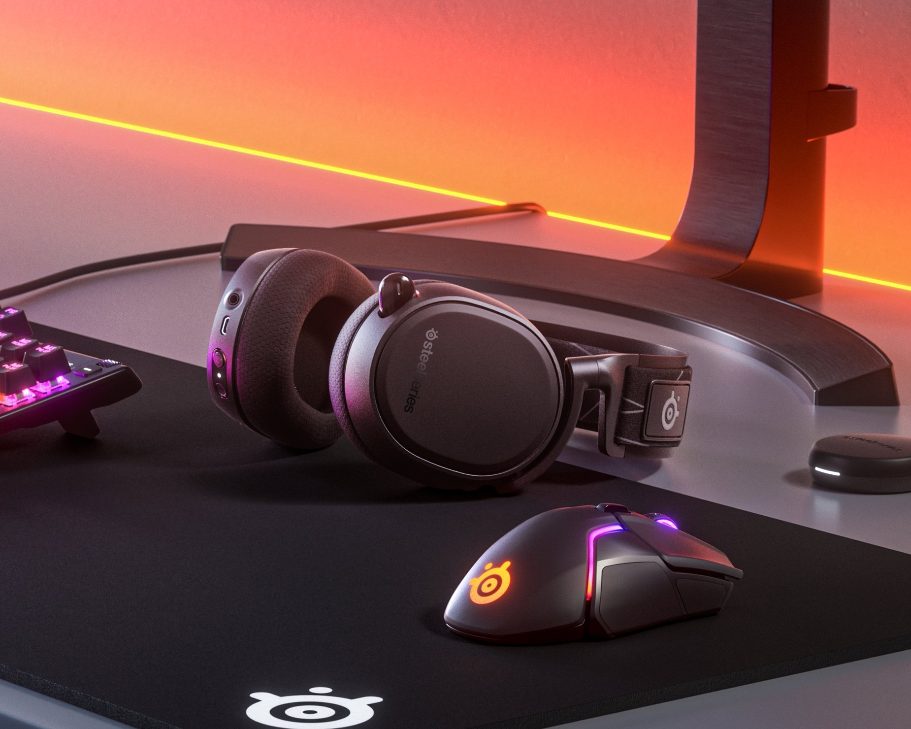 """Arctis 9 på ett skrivbord med annan kringutrustning """"Från skaparna bakom de bästa gamingheadsetsen för audiofiler"""" – IGN"""