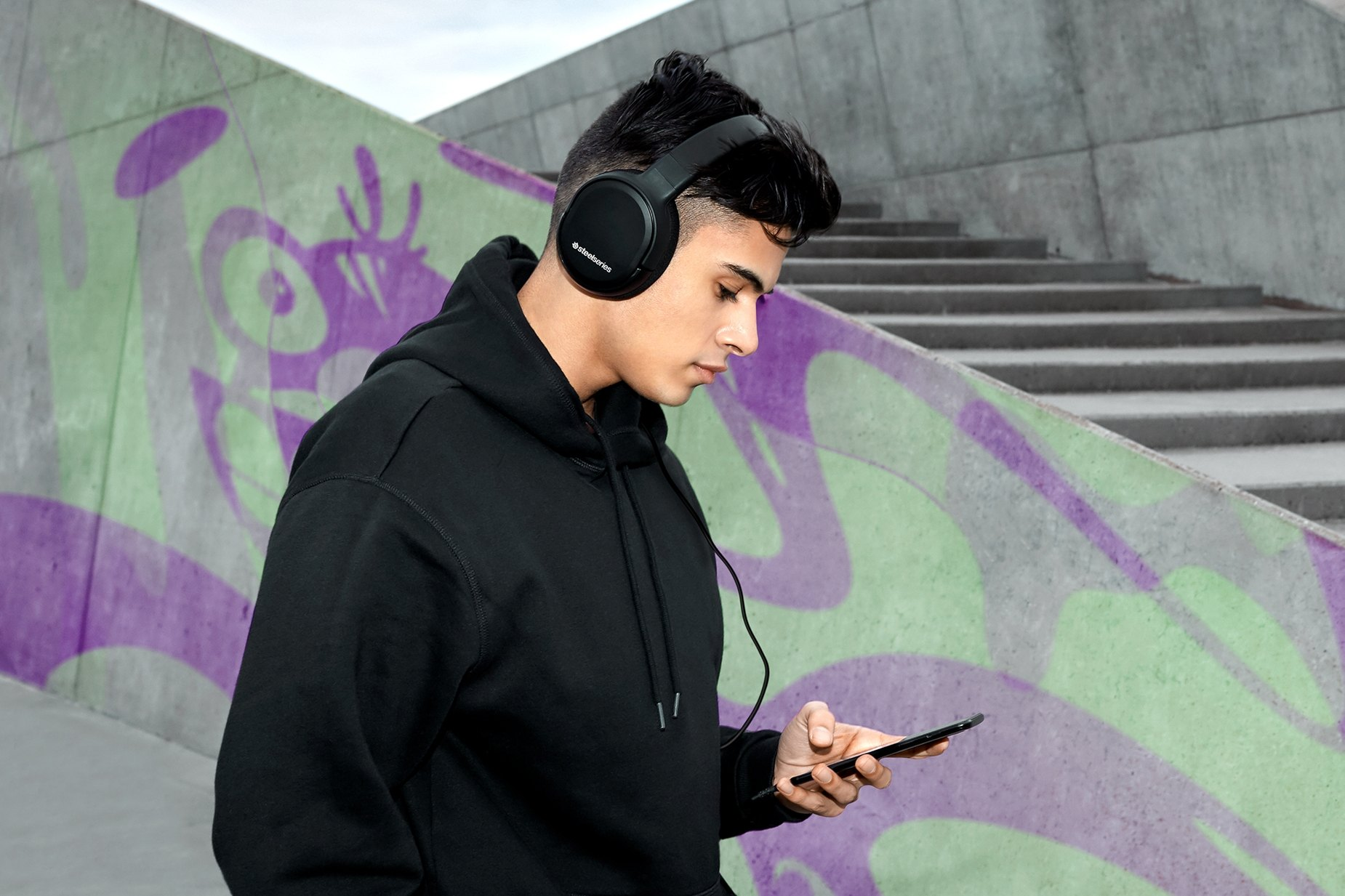 Gamer outdoors listening to music on a mobile device using the Arctis 1 gaming headset.