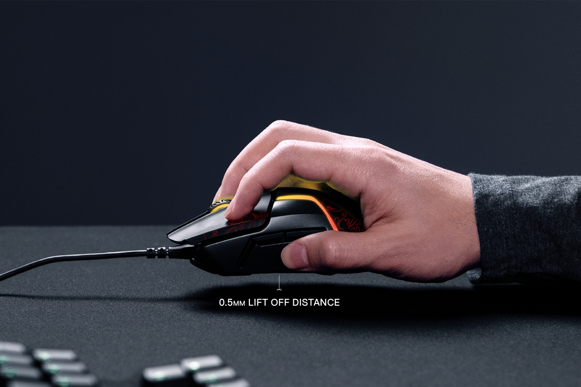 Hand holding Rival 600 Dota 2 Edition above table showing 0.5mm lift off distance
