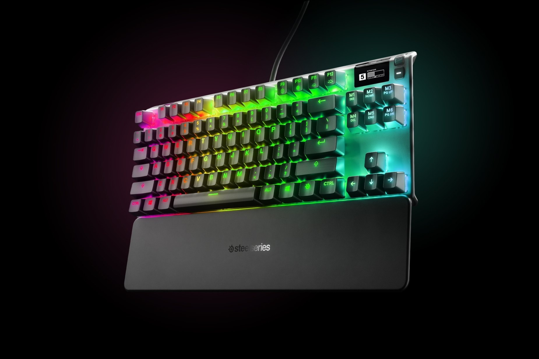 German - Apex Pro TKL gaming keyboard with the illumination lit up on dark background, also shows the OLED screen and controls used to change settings, switch actuation, and adjust audio
