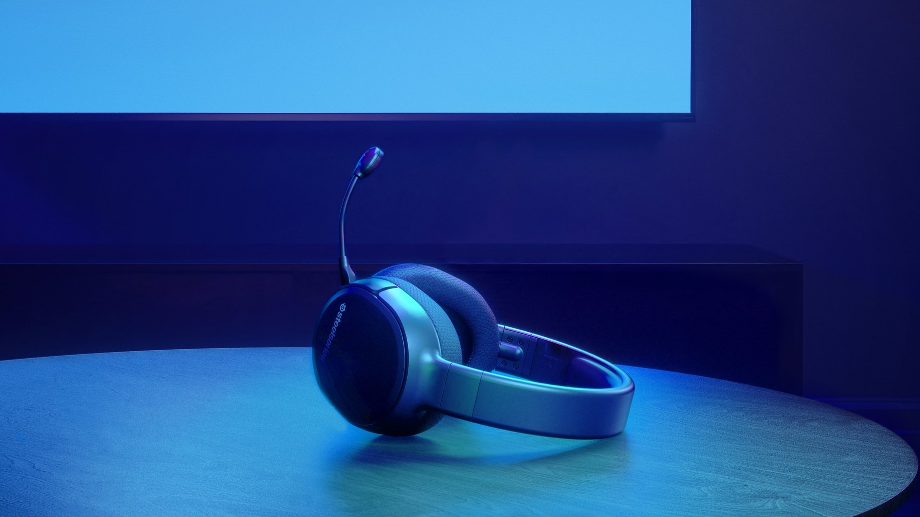 Arctis 1 Wireless for PS4 gaming headset on table with a Playstation controller and a PS4 in the background.