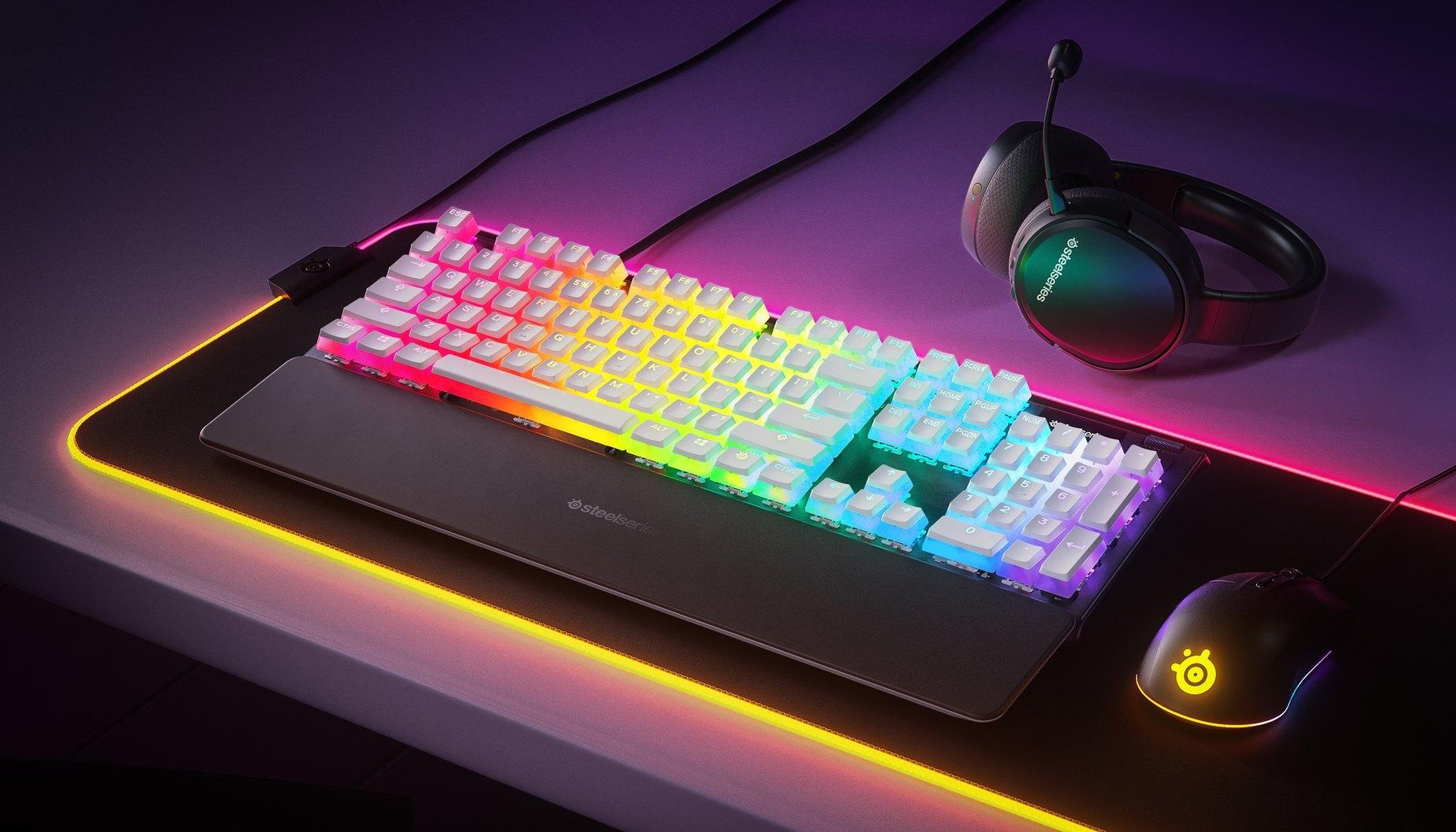 Touches Prismcaps sur un clavier Apex Pro, à côté d'une souris SteelSeries, d'un tapis de souris RVB et d'un casque audio Arctis. On peut voir l'illumination RVB à travers les touches de clavier.