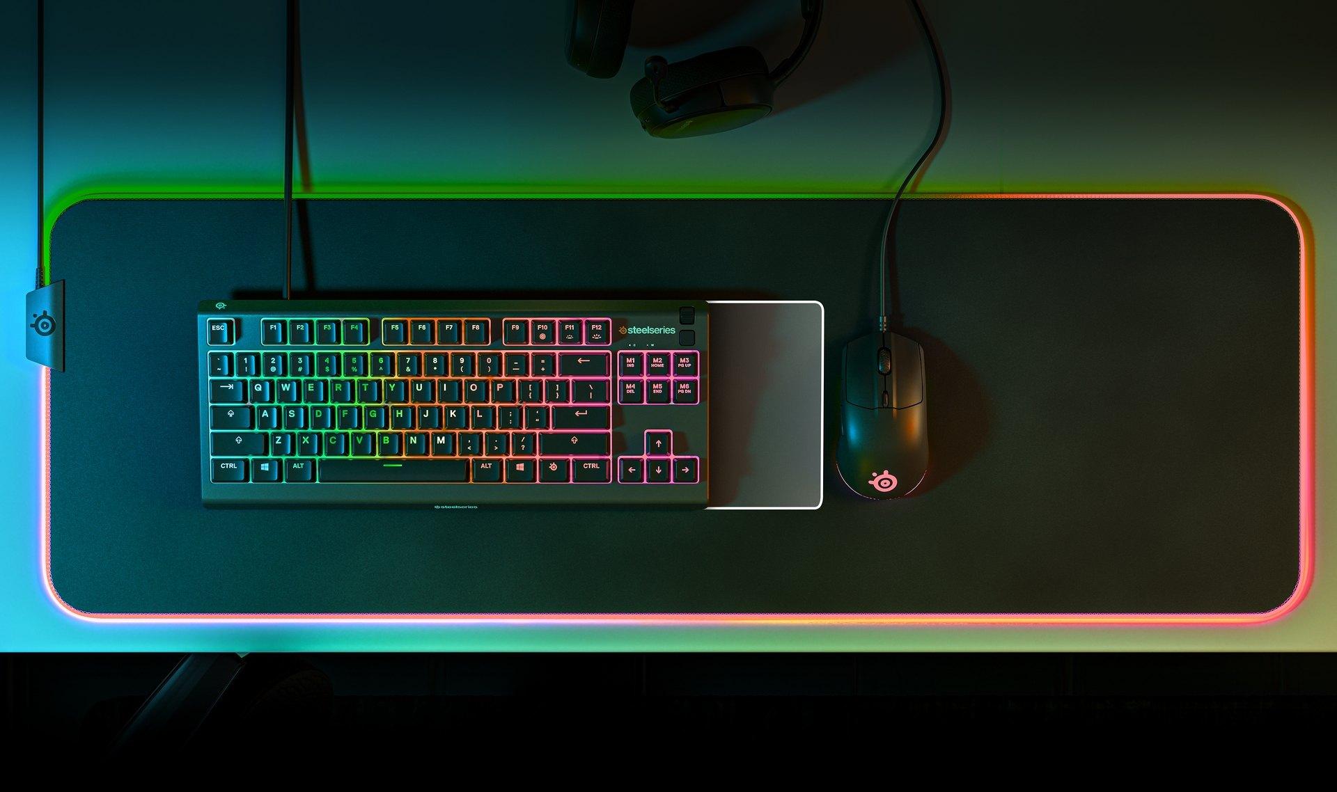 """""""Apex3TKL""""-Tastatur und SteelSeries-Maus auf einem beleuchteten QcK-Prism-Mauspad mit Stoffüberzug. Daneben liegt ein Arctis-Headset. Alle Geräten werden von der RGB-Beleuchtung angestrahlt."""