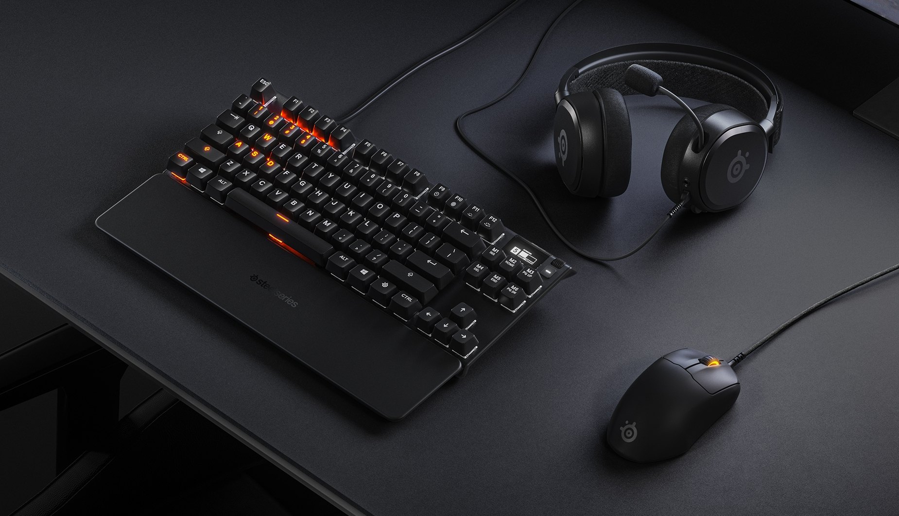 A sleek desktop setup with a Prime keyboard, mouse, and headset.
