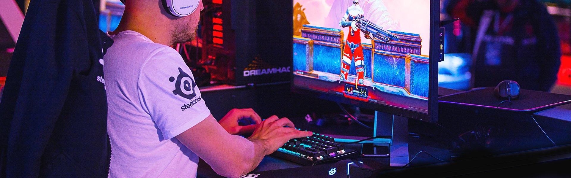 Profi-E-Sportler tippt auf Tastatur mit Rival600 auf Mauspad neben seiner Tastatur