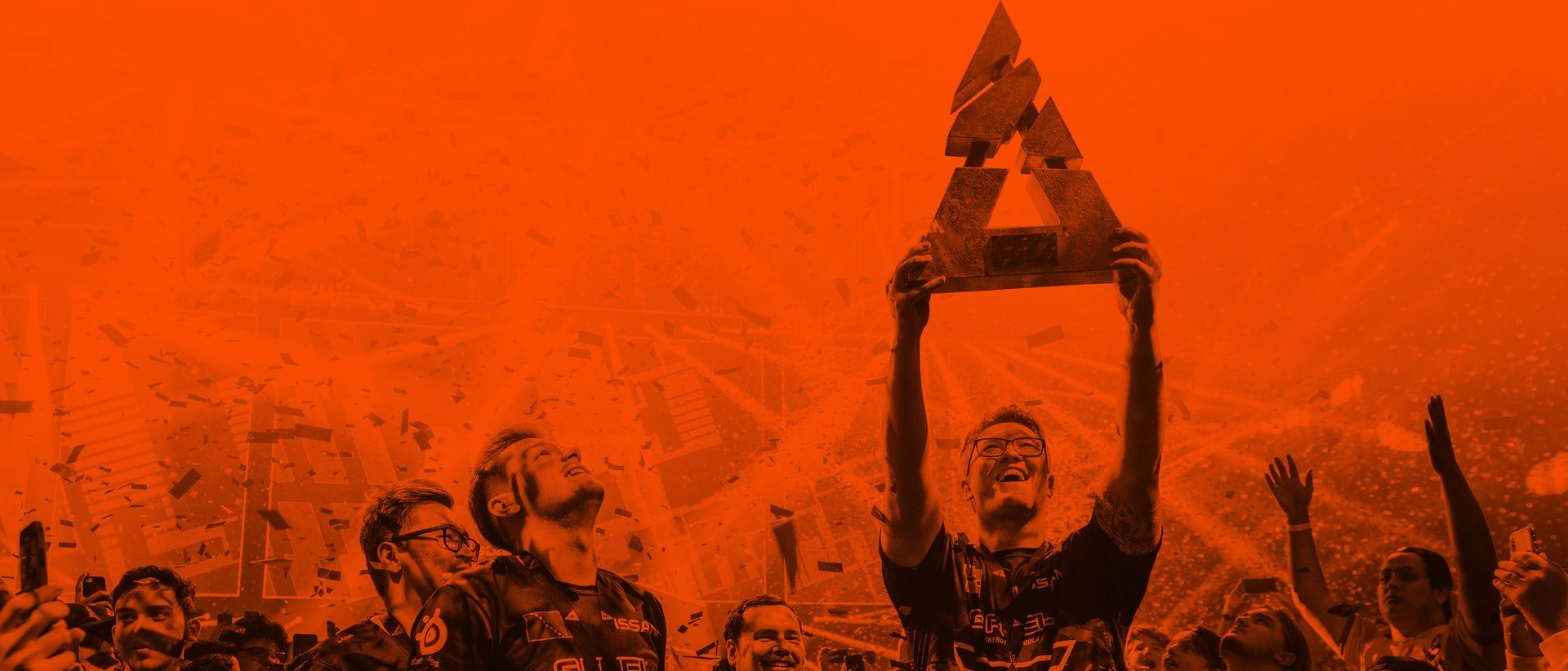 An esports player celebrates a win with a trophy above their head and confetti falling.