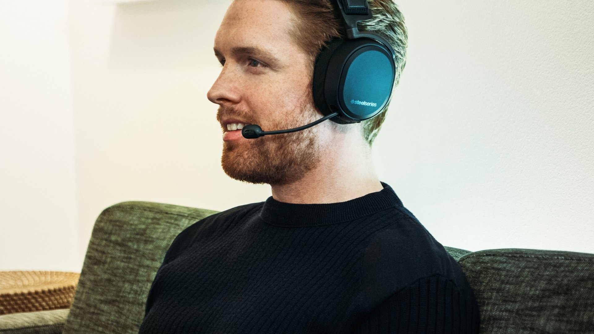 A gamer smiling while using the headset and playing a game