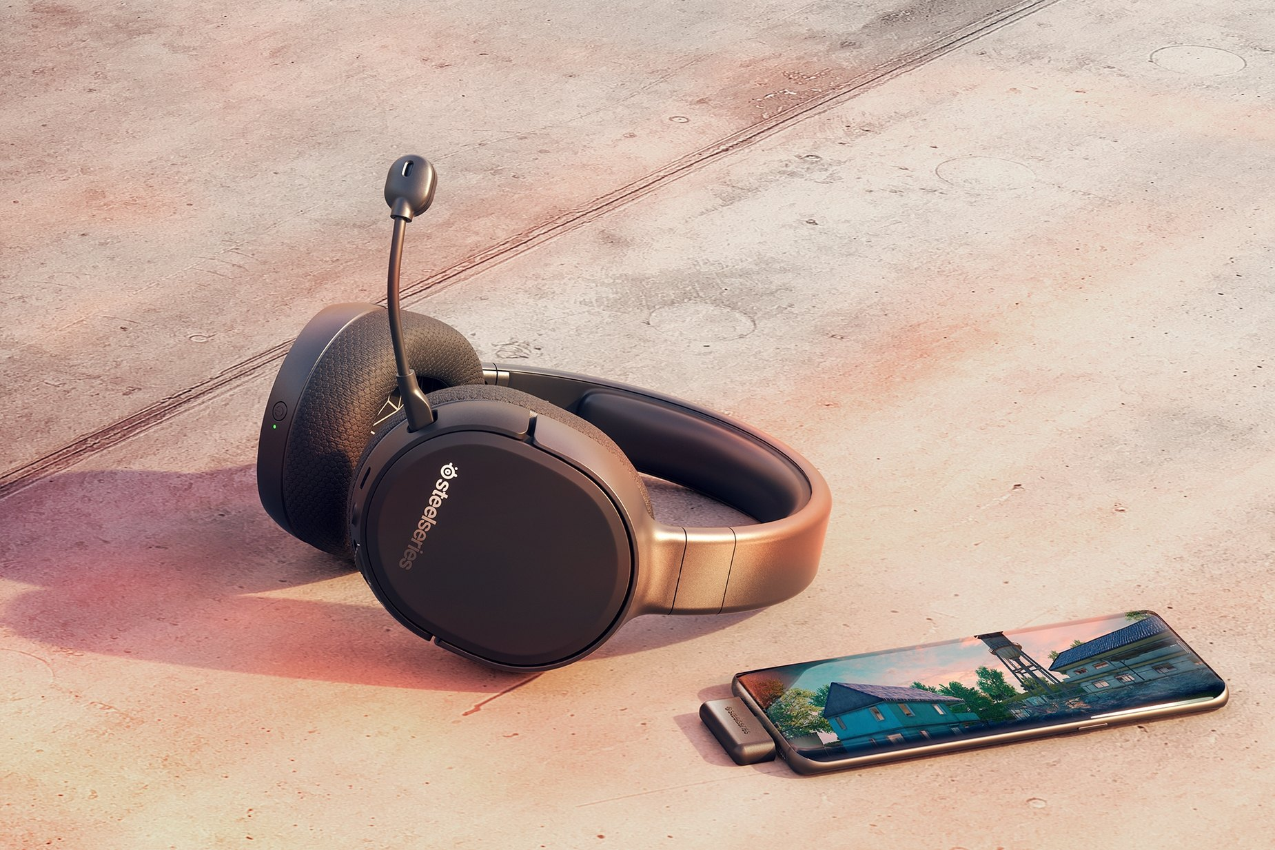 Arctis 1 Wireless gaming headset on surface next to a mobile device, connected via the wireless dongle