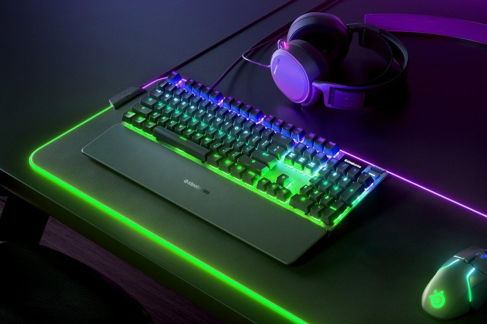 US English - Apex 7 (Red Switch) gaming keyboard on a desk with a gaming mouse, both on top of a large mousepad and a SteelSeries gaming headset next to them