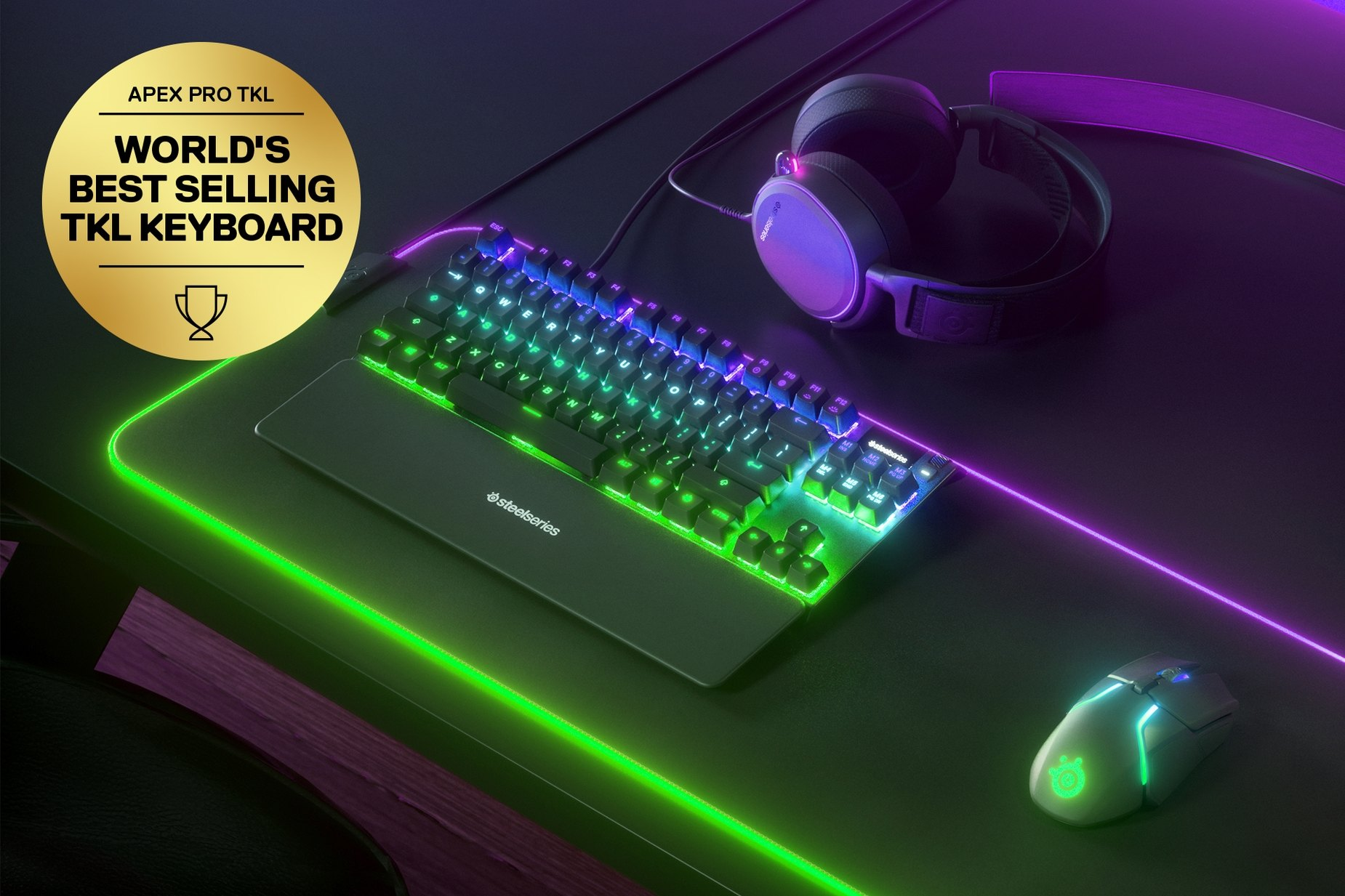 "German - Apex Pro TKL gaming keyboard on a desk with a gaming mouse, both on top of a large mousepad and a SteelSeries gaming headset next to them. Keyboard has gold award floating next to it with text ""World's best selling TKL Keyboard""."