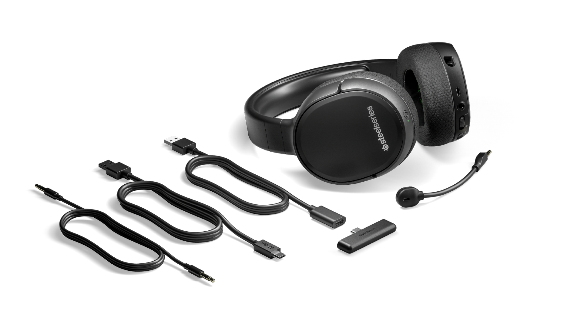 The Arctis 1 Wireless for Xbox gaming headset surrounded by all the box contents including extra cables and the wireless dongle