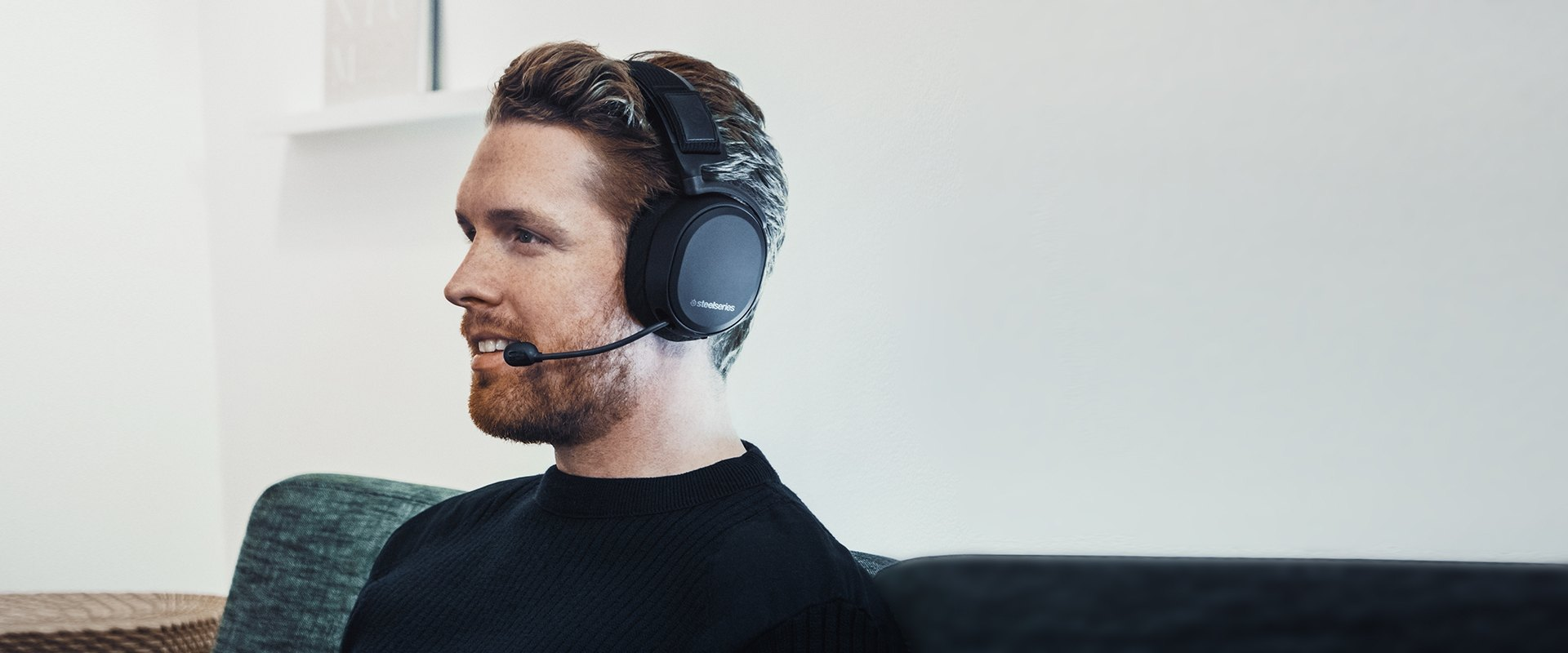 A user smiling while wearing the Arctis Pro Wireless, microphone in the extended position