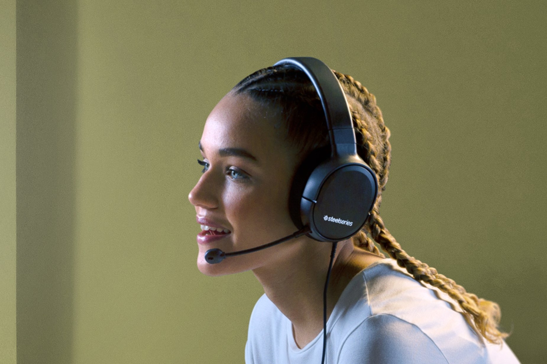 Gamer chatting with teammates via the Arctis 1 gaming headset microphone.