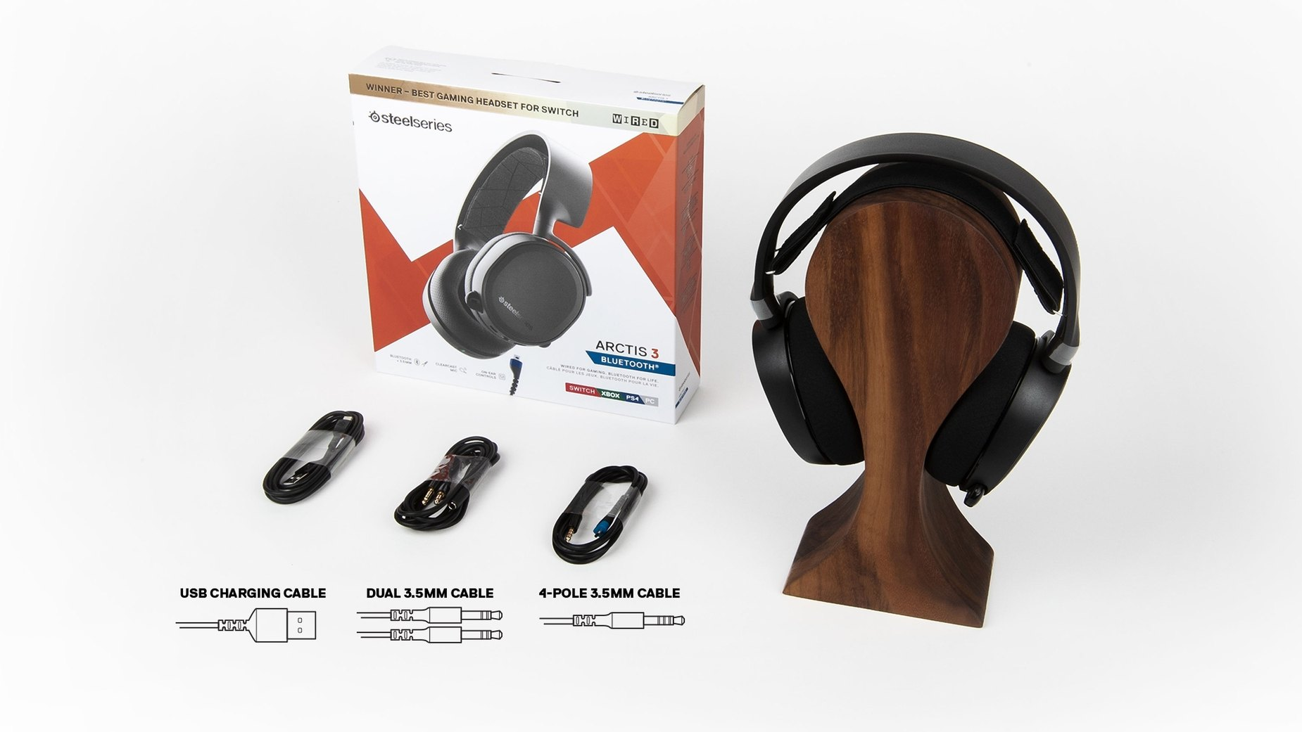 The Arctis 3 Bluetooth wireless gaming headset surrounded by retail package and box content including; USB charging cable, Dual 3.5mm cable, and 4-pole 3.5mm cable