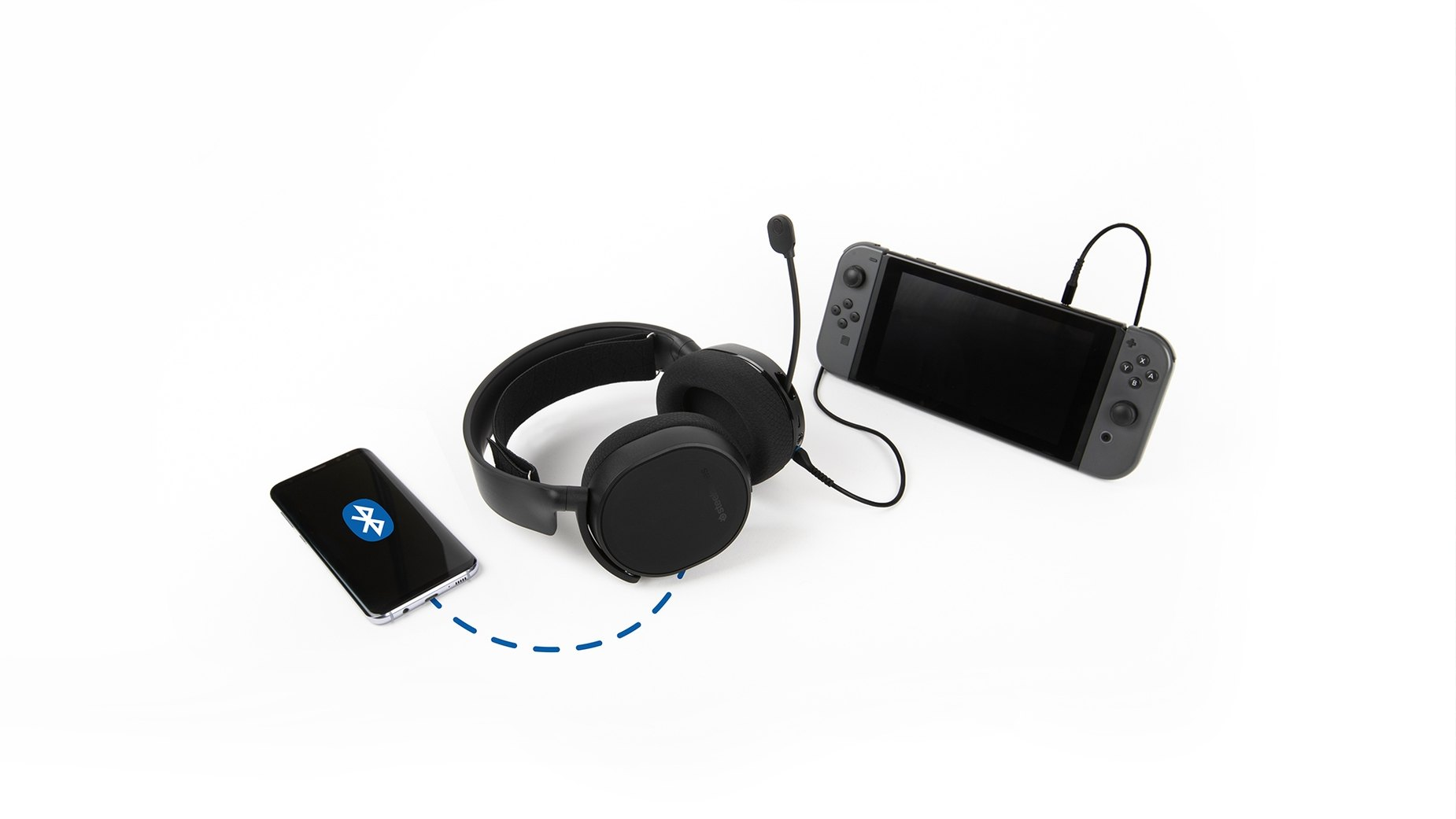 The Arctis 3 Bluetooth wireless gaming headset surrounded by Nintendo Switch game console and mobile device, connected wired to Nintendo Switch while simultaneously connected via Bluetooth to mobile device