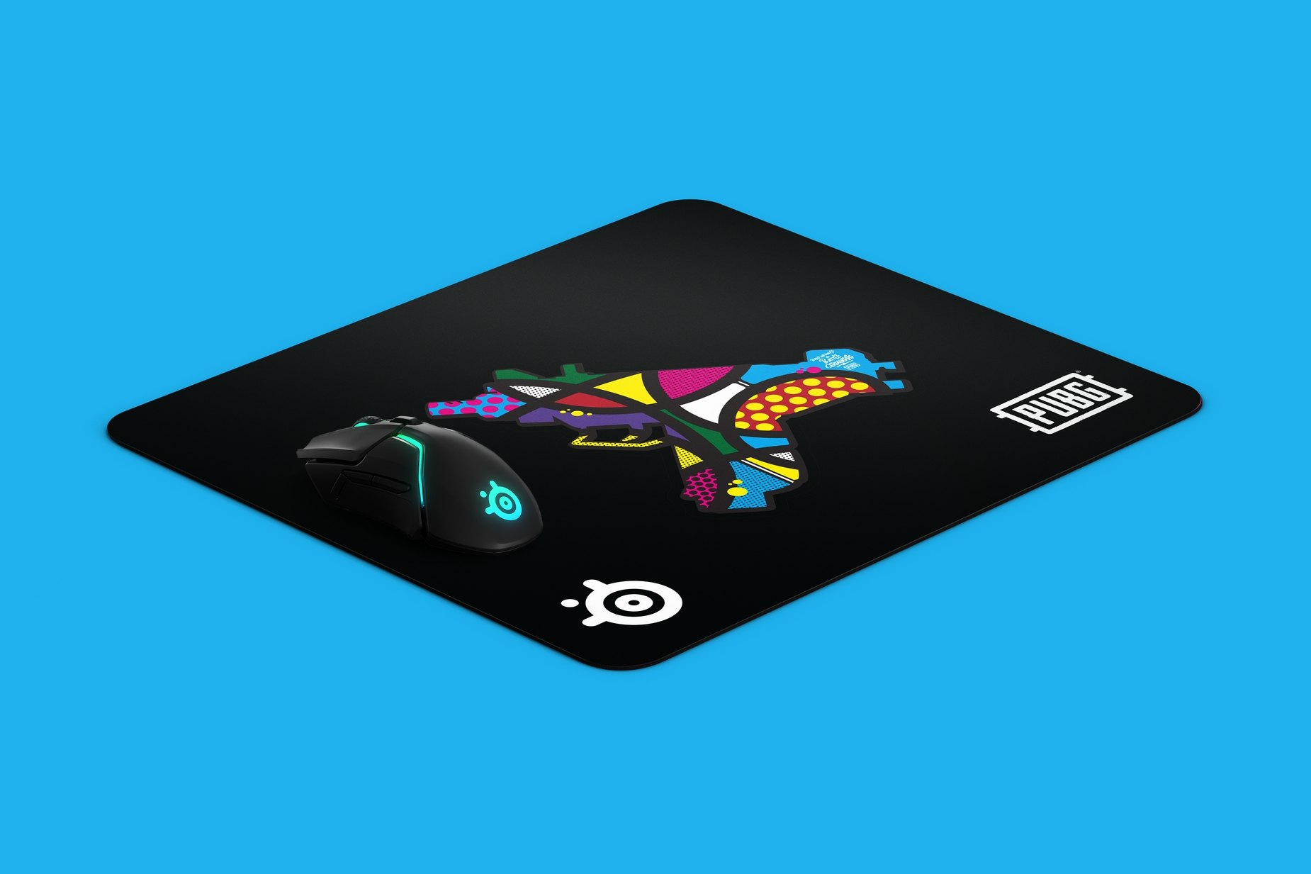 Image of a mousepad laying on a diagonal. Mousepad has a graffiti adorned uzi design. Mousepad has a Steelseries mouse on top of mousepad to display scale of mousepad.