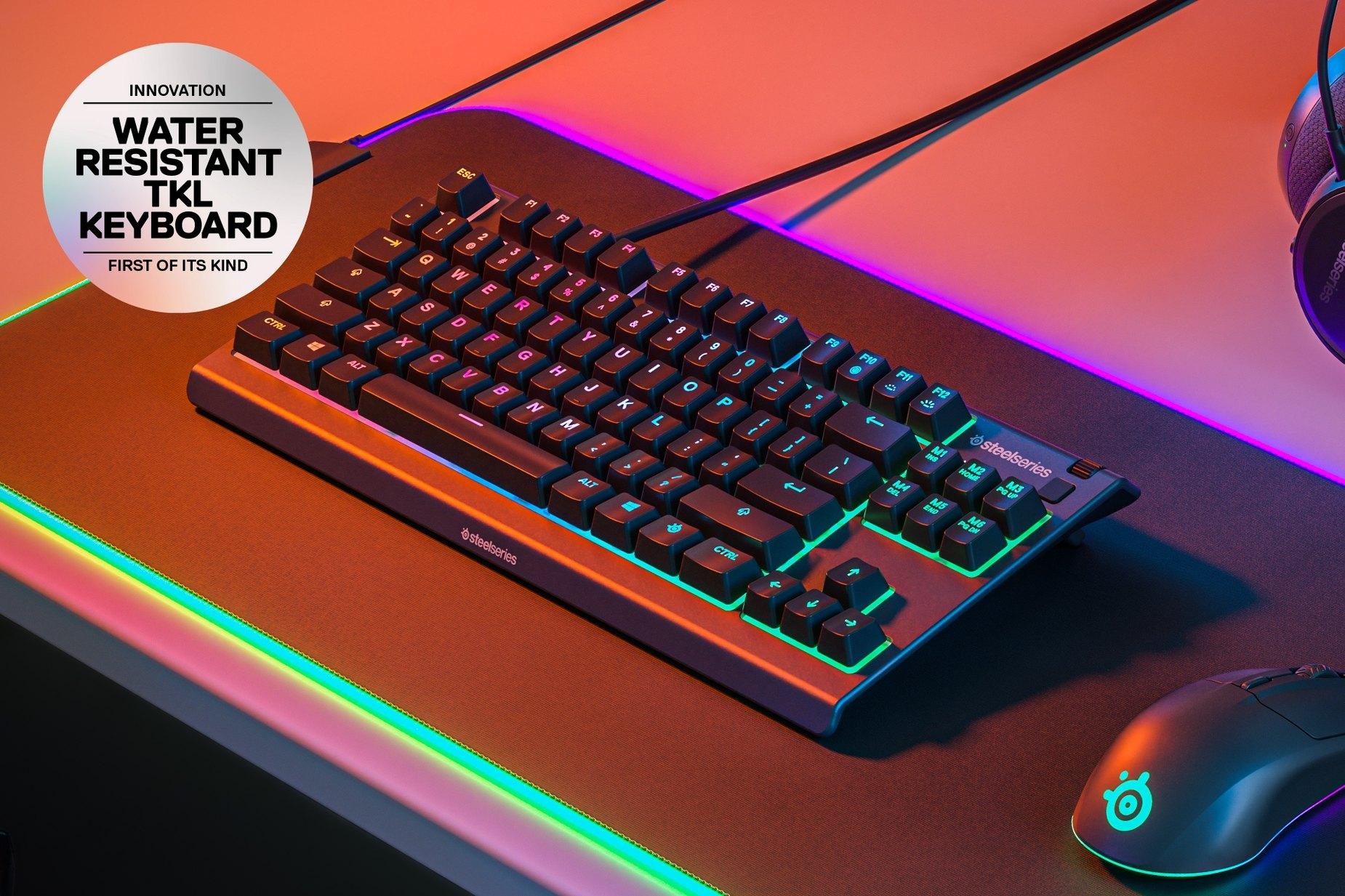 """""""Apex 3TKL""""-Tastatur von SteelSeries mit RGB-Beleuchtung auf einem Mauspad. In einem runden Textfeld steht: """"Innovation: Wasserfeste TKL-Tastatur: Die Erste ihrer Art."""""""