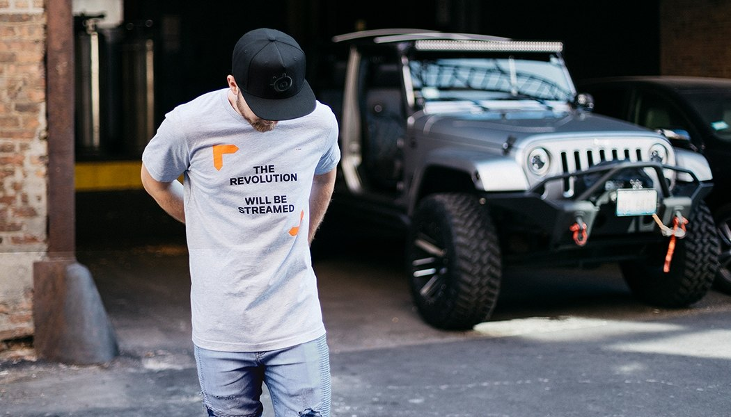 A model wearing the shirt with an SUV in the background