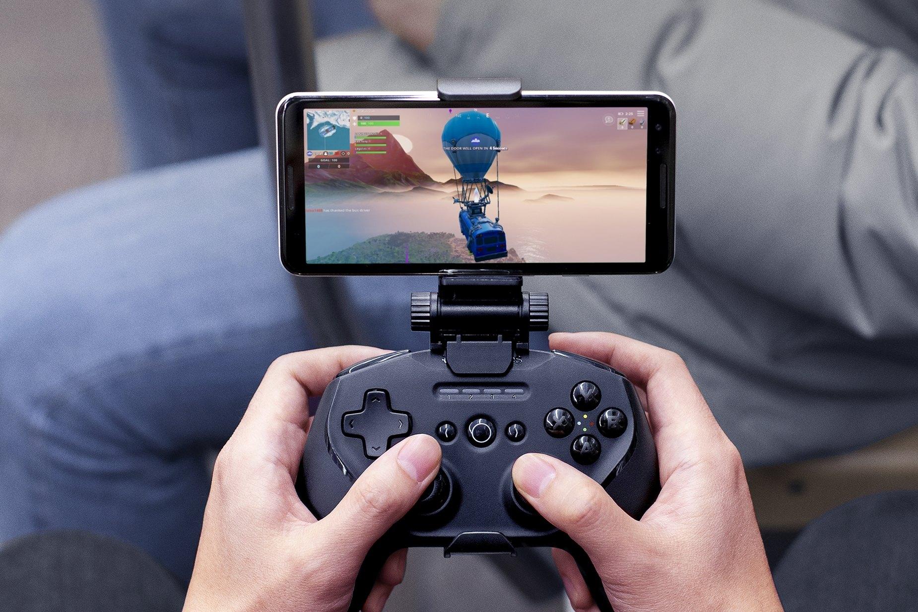 Des mains tenant une manette Stratus Duo avec une fixation SmartGrip pour téléphone en train de jouer à Fortnite sur mobile