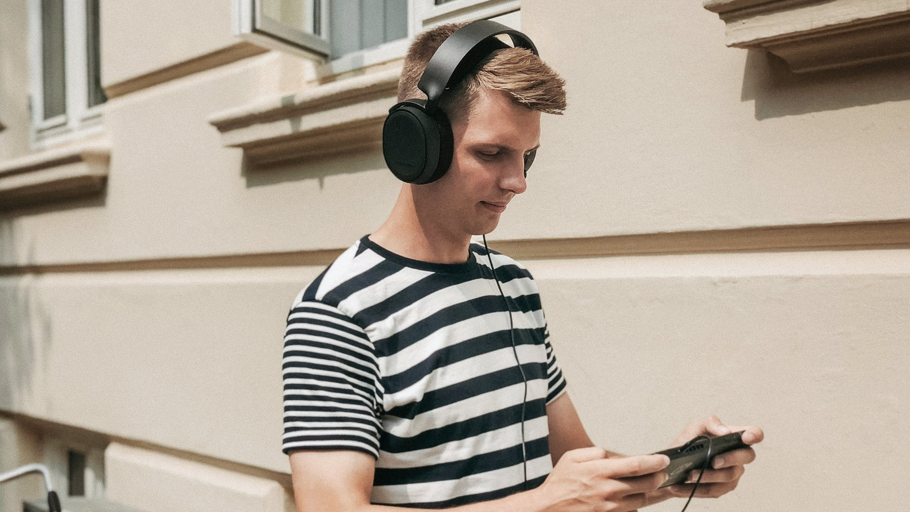 Gamer outdoors playing the Nintendo Switch game console while listening via the Arctis 1 Bluetooth gaming headset connected via 3.5mm mobile cable